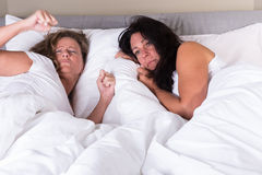 Two attractive women waking up next to each other in bed Royalty Free Stock Images