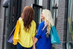 Two attractive women walking holding hands along the street Stock Photos