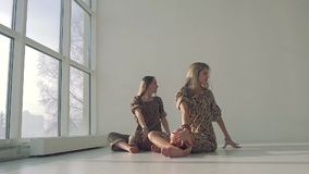Two attractive women wearing yoga clothes practicing yoga poses stock video footage