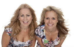 Two Attractive Young Adult Women Smiling. Studio photo of two attractive blonde women smiling at camera. Windblown hair, white background royalty free stock images