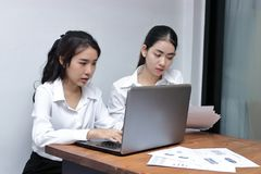 Two attractive young Asian businesswoman using laptop together in modern office. Team work business concept. Two attractive young Asian businesswoman using Stock Photo