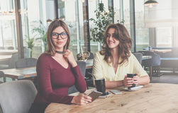 Two attractive young brunette women sit in cafe at table and drink coffee. Meeting friends at restaurant. Colleagues have a rest after work. Blurred background stock image
