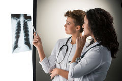 Two attractive young doctors looking at x-ray Royalty Free Stock Image