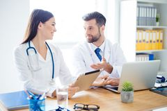Two attractive young doctors using computer and discussing  thei. R viewpoints about innovations in medicine with each other Royalty Free Stock Photo