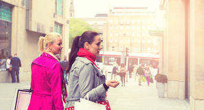 Two attractive young female friends enjoying a day out shopping, colorised image Royalty Free Stock Image
