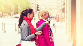 Two attractive young female friends enjoying a day out shopping, colorised image Stock Photo