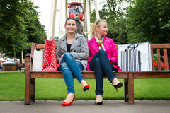 Two attractive young female friends enjoying a day out after successful shopping Royalty Free Stock Photo