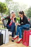 Two attractive young female friends enjoying a day out after successful shopping Royalty Free Stock Image