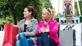 Two attractive young female friends enjoying a day out after successful shopping Stock Images