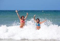 Two attractive young girl friends playing in the sea on vacation Royalty Free Stock Photography