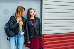Two attractive young girl friends standing together and posing on camera. Outdoors fashion portrait young pretty best girls friend. S in friendly hug. Walking at Royalty Free Stock Images