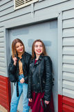 Two attractive young girl friends standing together and posing on camera. Outdoors fashion portrait young pretty best girls friend. S in friendly hug. Walking at Royalty Free Stock Image