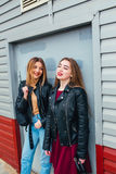 Two attractive young girl friends standing together and posing on camera. Outdoors fashion portrait young pretty best girls friend. S in friendly hug. Walking at Royalty Free Stock Photography