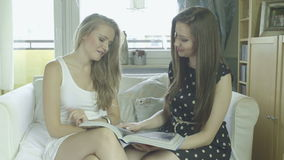 Two attractive young girlfriends watching fashion magazine stock video
