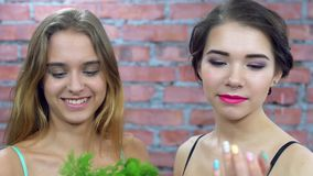 Two attractive young girls in bra smiles on camera. Green parsley. Casting. Brick wall on background stock video footage