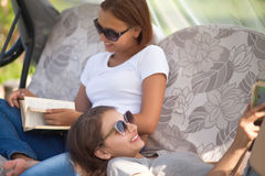 Two attractive young girls reading and relax Stock Photo