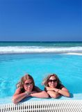Two attractive young girls in a swimming pool on the beach Stock Images