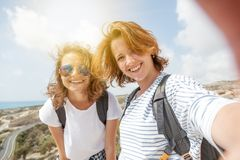 Two attractive young girls travel together, do selfie on the pho royalty free stock photo