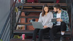 Two attractive young office workers analysing the plan of work using the notebook and tablet while sitting on office