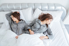 Two attractive young sisters twins sleeping in bed Stock Photo