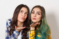 Two attractive young woman with shiny makeup sending air kiss, looking at camera, on white background stock image