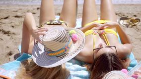 Two attractive young woman sunbathing. In their bikinis at the seaside lying on their backs on towels in the sand   close up head to toe view stock video footage