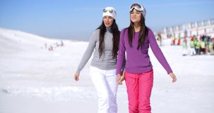Two attractive young woman walking in fresh snow. At a winter ski resort chatting and smiling together in the sunshine  with copy space stock footage