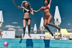 Crazy girls. Two attractive young women in bikini holding hands and keeping mouths open while jumping in the pool outdoors Royalty Free Stock Photo