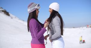 Two attractive young women chatting in the snow. Two attractive young women standing chatting in the snow at a mountain resort in winter  close up side view stock footage