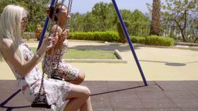 Two attractive young women chatting on swings stock footage