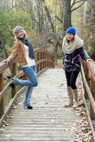 Two attractive young women laughing on a wooden bridge Stock Images
