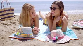 Two attractive young women laying sunbathing. On a tropical beach chatting and smiling as they lie on their towels stock video footage