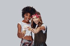 Two attractive young women. Looking at camera and smiling while standing against grey background stock photos