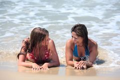 Two attractive young women lying on a sunny beach near the water Royalty Free Stock Photography