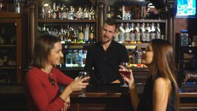 Two attractive young women meeting up in a pub for a glass of red wine sitting at a counter smiling at each other stock footage