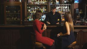Two attractive young women meeting up in a pub for a glass of red wine sitting at a counter smiling at each other stock video