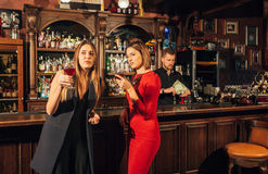 Two attractive young women meeting up in a pub for glass of red wine sitting at counter smiling each other Stock Image