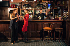 Two attractive young women meeting up in a pub for glass of red wine sitting at counter smiling each other Royalty Free Stock Images