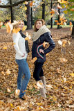 Two attractive young women posing with falling leaves Stock Images