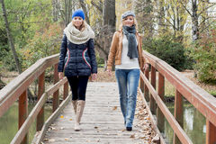 Two attractive young women posing on a wooden bridge Stock Images