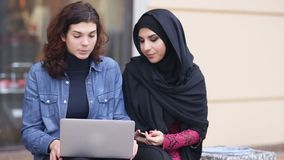 Two attractive young women sitting outside and using laptop. Cross-cultural friendship. Young muslim woman in black. Hijab is talking to her female caucasian stock footage