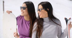 Two attractive young women with their snowboards Stock Images