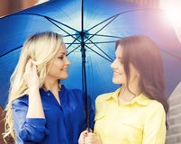 Two attractive young women with an umbrella Royalty Free Stock Images