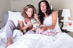 Two attratcive women sitting in bed and viewing TV Royalty Free Stock Photo