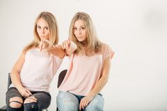 Two attrative sisters twins pointing over white background. Two cheerful attrative sisters twins pointing over white background Stock Photos