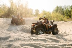 Two atv riders in helmets ride in a circle on sand stock photo