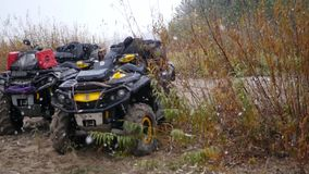 Two ATV standing on the bank of the river near the fall, it`s snowing. slow motion stock video