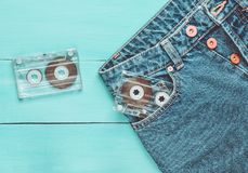Two audio cassettes in a jeans pocket on a blue wooden surface. Media technology from the 80s. Two audio cassettes in a jeans pocket on a blue wooden surface stock photos
