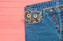 Two audio cassettes in a jeans pocket on a pink wooden surface. Media technology from the 80s.  stock photo