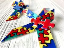 Autism awareness ribbons. Two autism awareness ribbons on a white wood background royalty free stock images